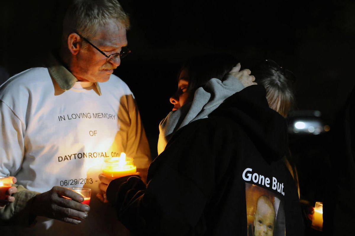 Keelie Cook receives a hug from family as her father-in-law Christopher, left, was on hand during a candlelight vigil for 3-month-old Dayton who passed away from injuries resulting in a car accident. The vigil was held at 8 p.m. (same time as Dayton's bed