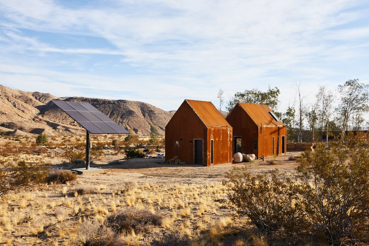 Two steel cabins in desert with solar power tree