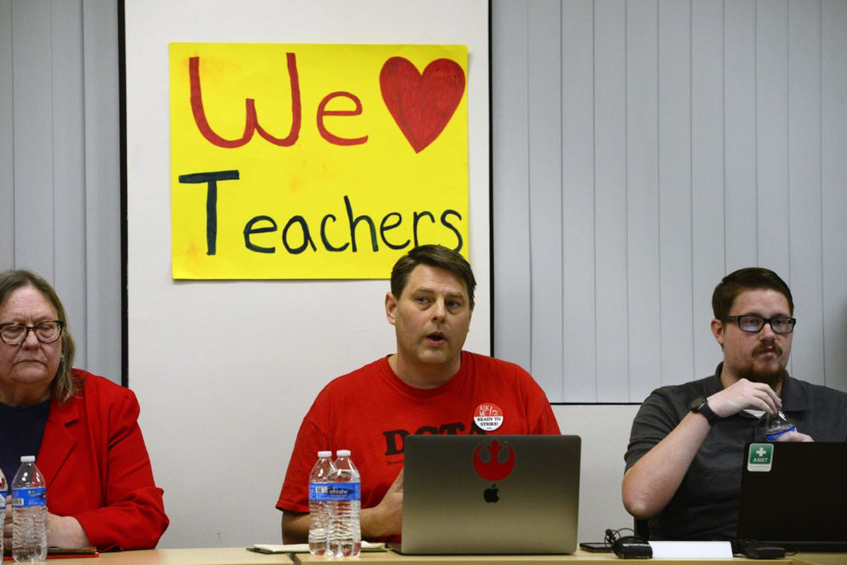 DCTA lead negotiator Rob Gould, wearing a red T-shirt, speaks as he sits between a man and a woman and in front of a We (heart) Teachers poster.