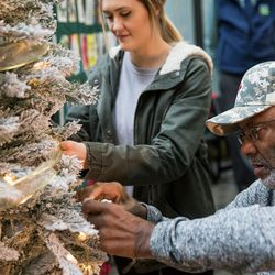 Madison Richardson, who received donated corneas, and Keith Robinson, who is waiting for a kidney transplant, hang ornaments on a Christmas tree at a ceremony hosted by Intermountain Donor Services in Salt Lake City on Wednesday, Dec. 21, 2016.