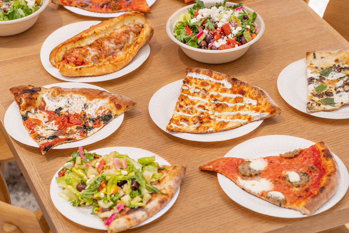 A side-angle view of pizza slices and salads on a wooden table.