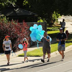 Community members gather to tie ribbons and write messages to the Rackley family and first responders of the murder-suicide along Alta Canyon Drive in Sandy on Saturday, June 10, 2017.
