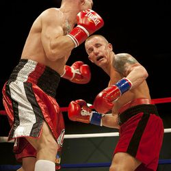 """Allen Litzau, right, takes a blow from Chris """"KidKayo"""" Fernandez during their boxing match at the South Towne Expo Center. Fernandez won the bout after four rounds, Saturday, Dec. 15, 2012."""