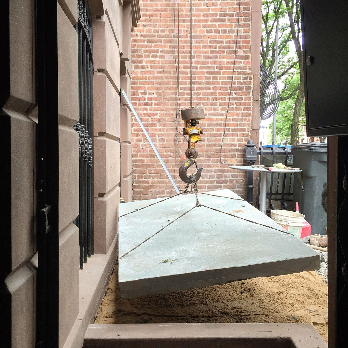 A bluestone paver being lowered into place in the front courtyard enclosure.