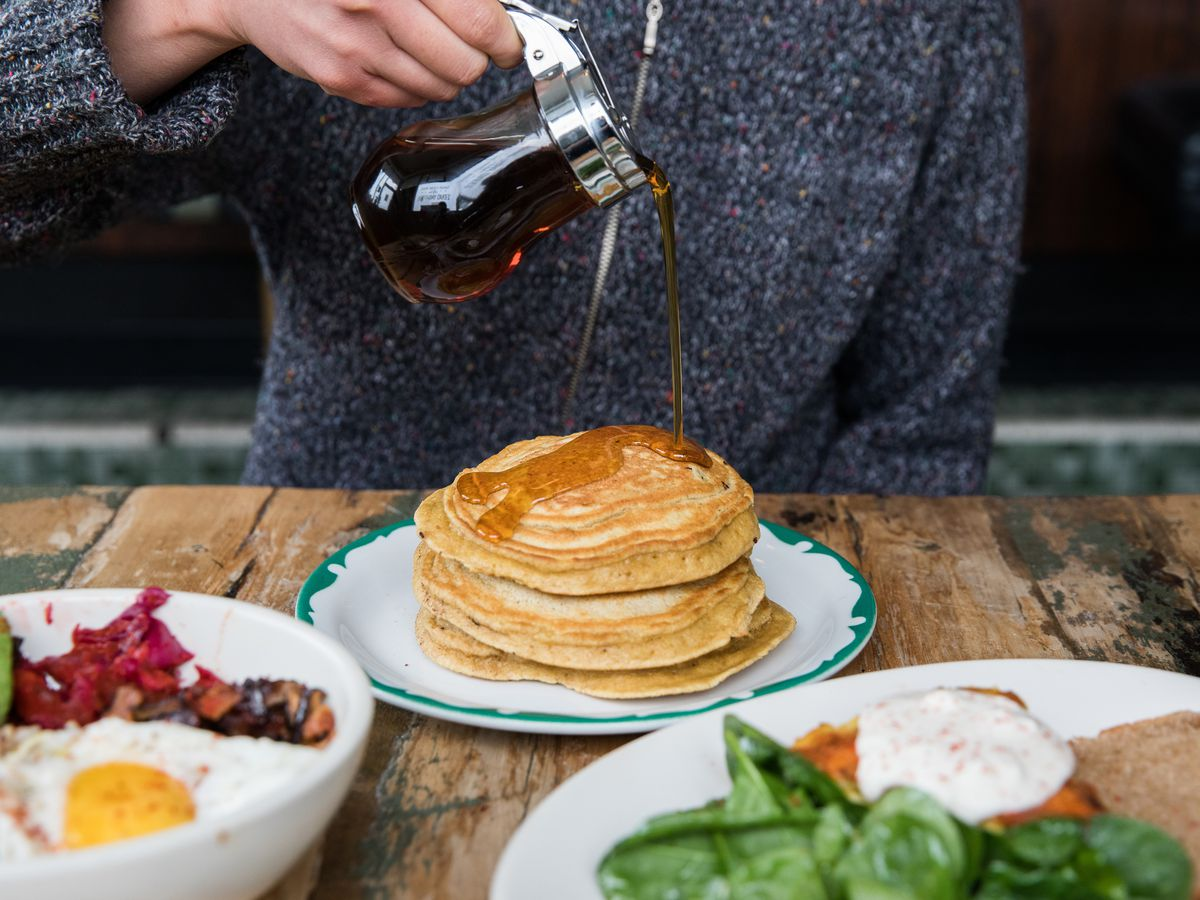 Someone in a gray sweater pours syrup over a stack of pancakes.