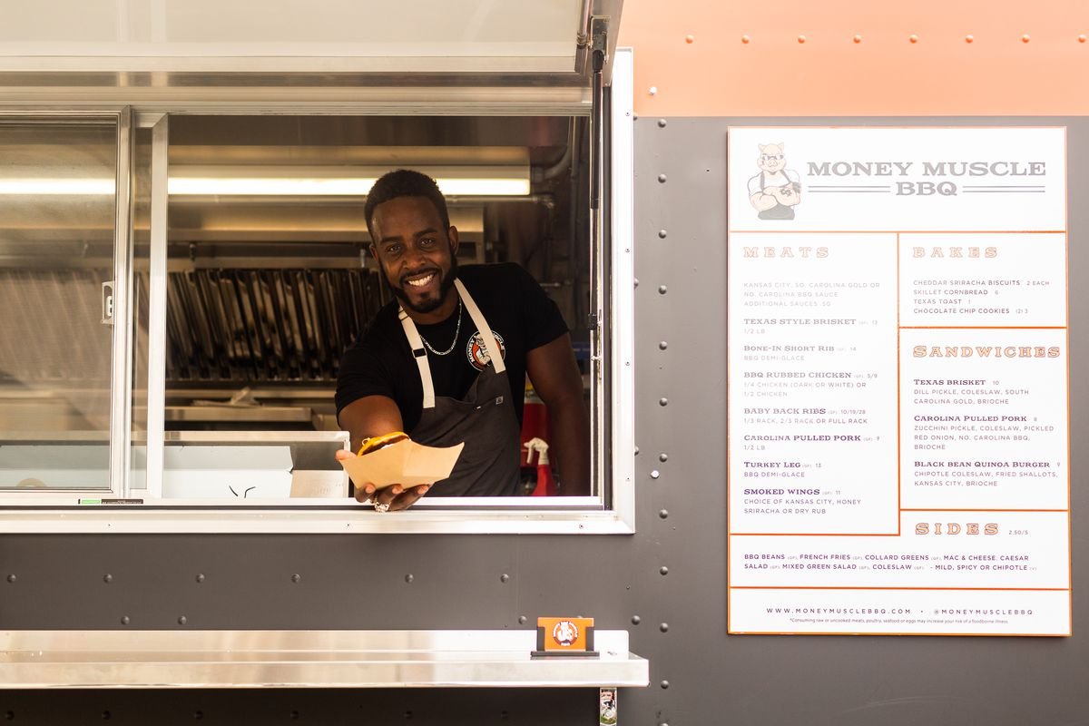 Chef Edward Reavis holds out a takeout tray from the serving window at his new Money Muscle BBQ truck