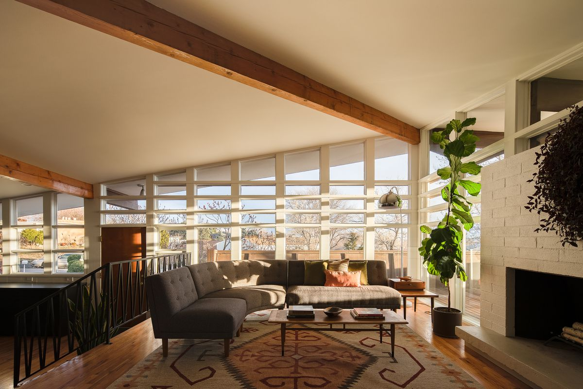 A living area with a large grey couch and a patterned area rug which sits on top of a hardwood floor. There are floor to ceiling windows and a fireplace.