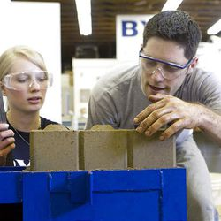 Emily Savage and Joran Booth examine a freshly pressed block from their project. After a day in the sun, it will be ready for building. The project will be used to build homes in Kenya.