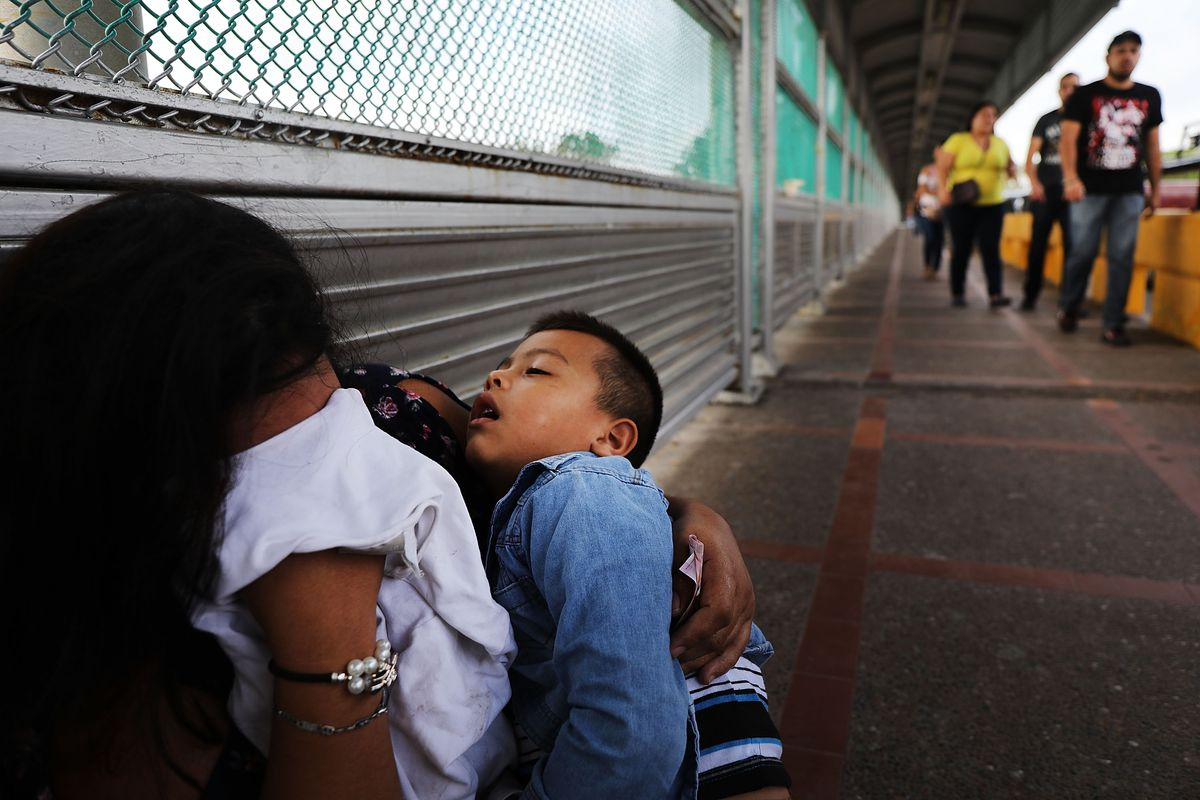 A crying Honduran woman and her child wait along a border bridge after being denied the chance to request asylum in the Texas city of Brownsville on June 22, 2018.