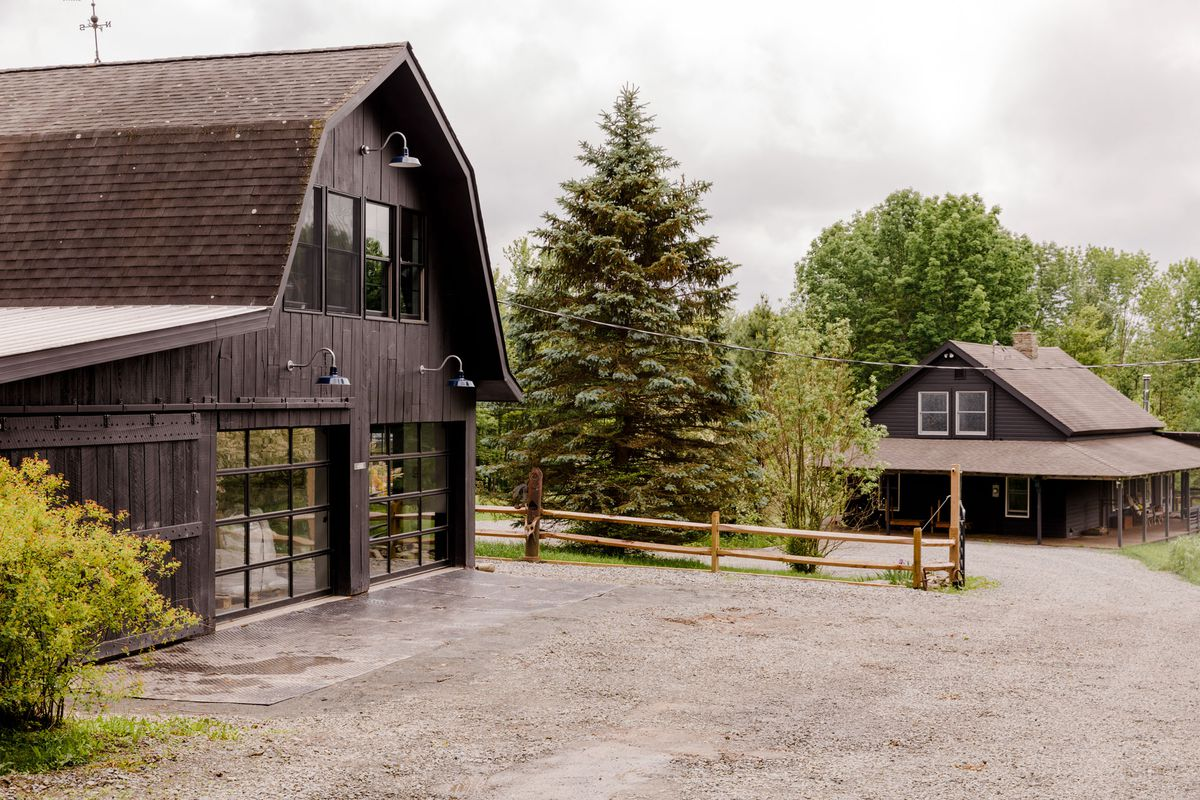 The exterior of a barn painted dark brown surrounded by trees overlooking Claire Marin's house