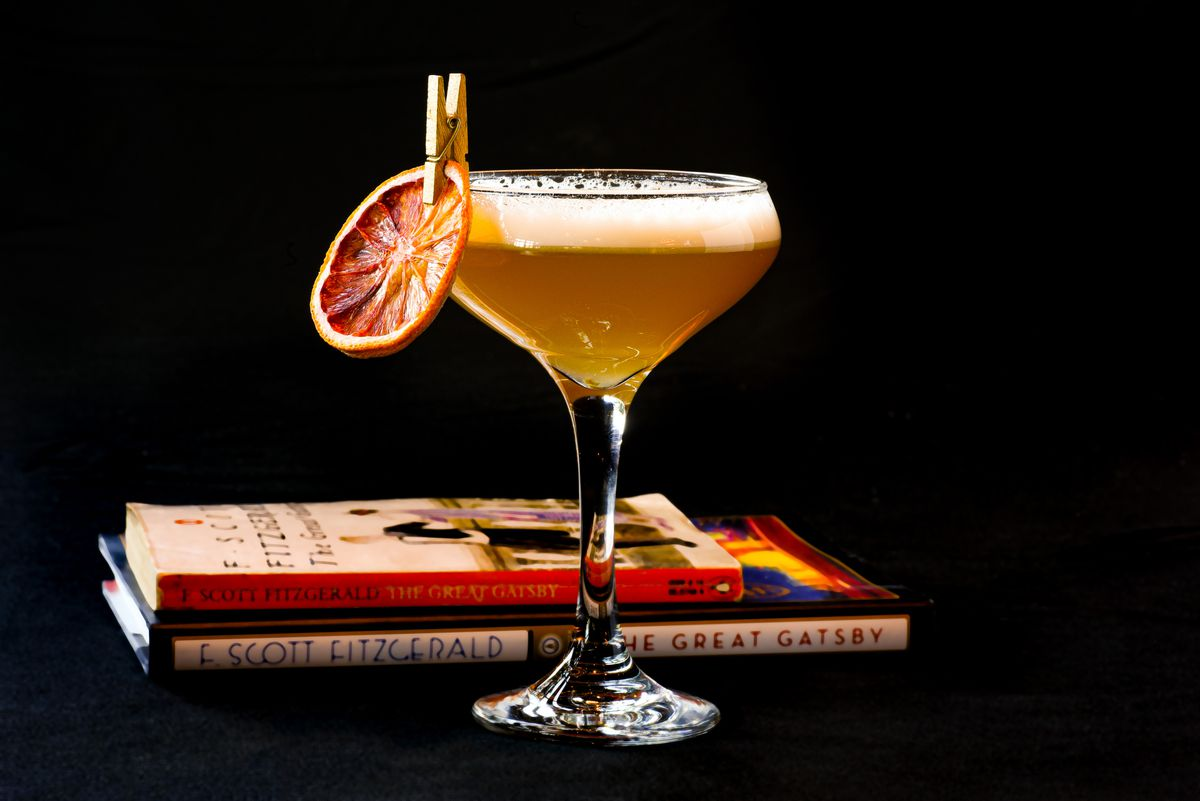 A cocktail in a coupe with books in the background