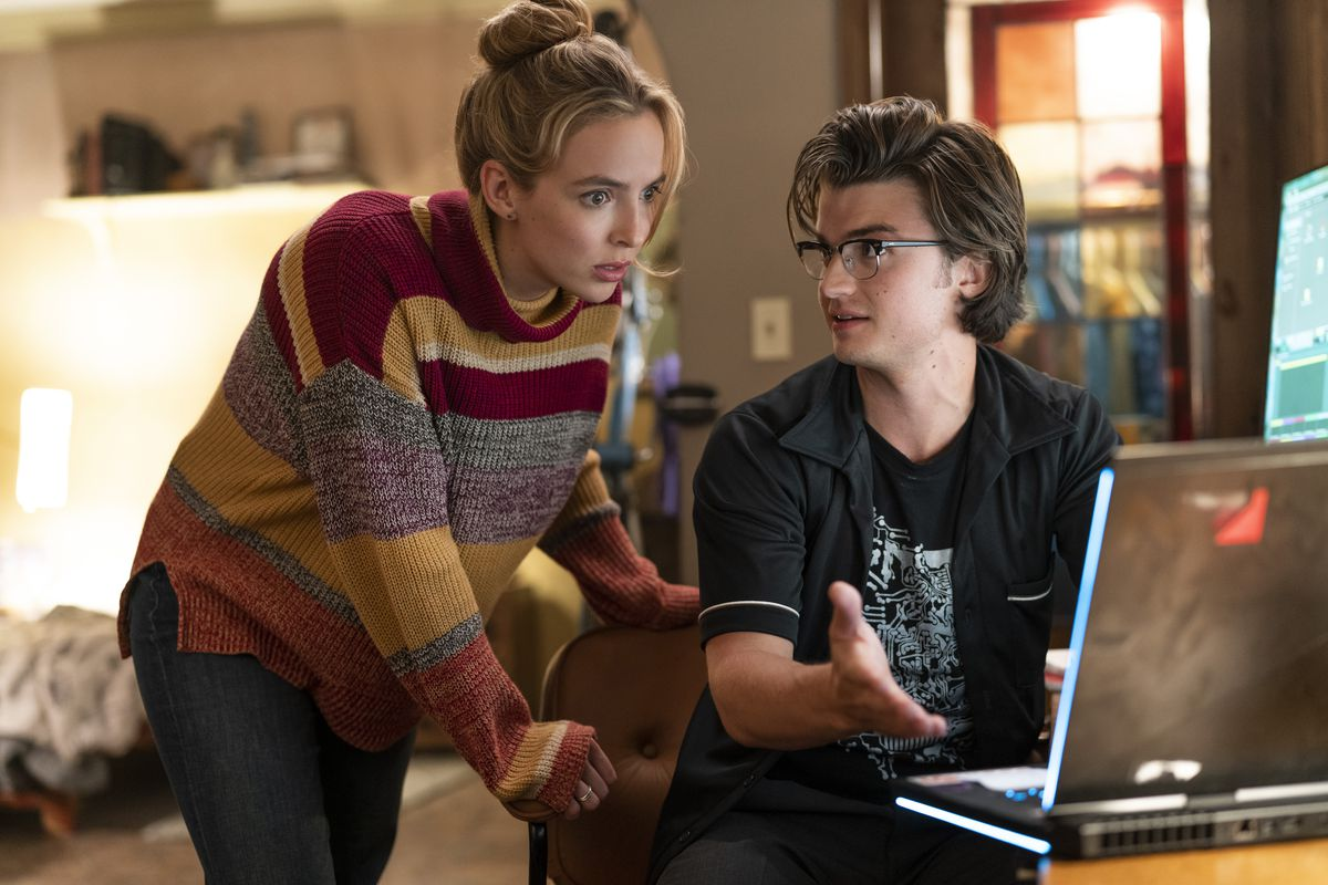 A young man gestures at a computer screen while a woman looks at it with a look of shock on her face.