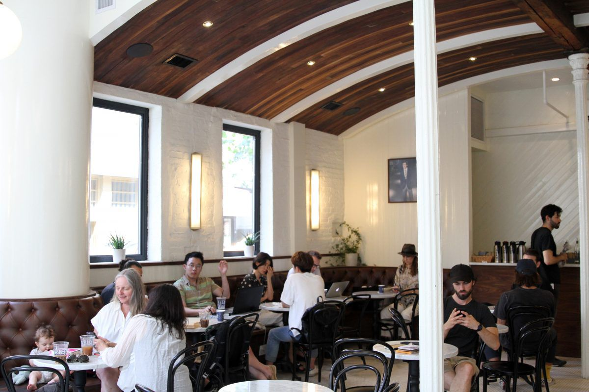 Several groups of people sitting inside Variety at various tables, under arched, high ceilings and near tall windows
