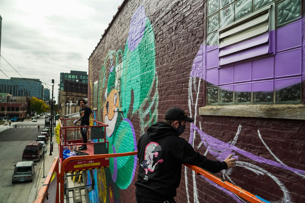 """At left, Reddor Santiago works on his character """"Kid Red"""" wearing a """"mecha-suit."""" At right, Blake Jones fills in the outline of his purple rabbit."""