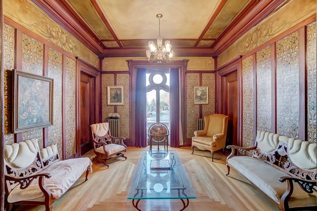 A formal living room has a chandelier, gold and mauve wallpaper, and formal couches.