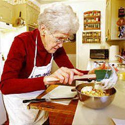 Winnifred Jardine prepares pot roast, salad and pineapple in her kitchen.