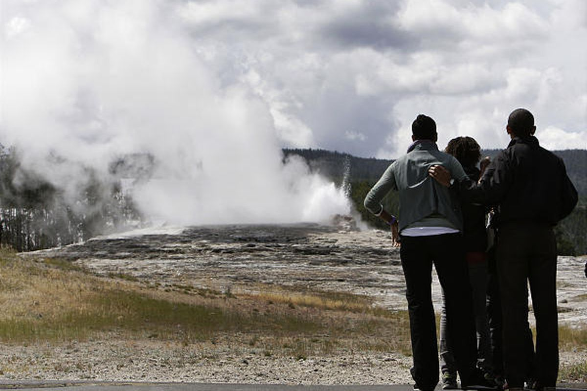President Barack Obama, his wife, Michelle, and their daughters, Malia, 11, and Sasha, 8, watch and wait for the Old Faithful geyser to roar to life at Yellowstone National Park during their visit there on Saturday.