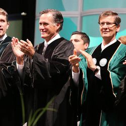 Former presidential candidate and Massachusetts Gov. Mitt Romney claps for graduates at Utah Valley University with UVU President Matthew Holland, UVU Board Chairman Steve Lund and Pamela Atkinson at Utah Valley University in Orem on Thursday, April 30, 2015.