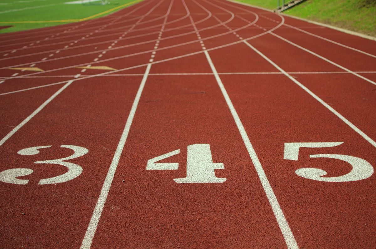 Photo of track lane numbers at an athletics track.
