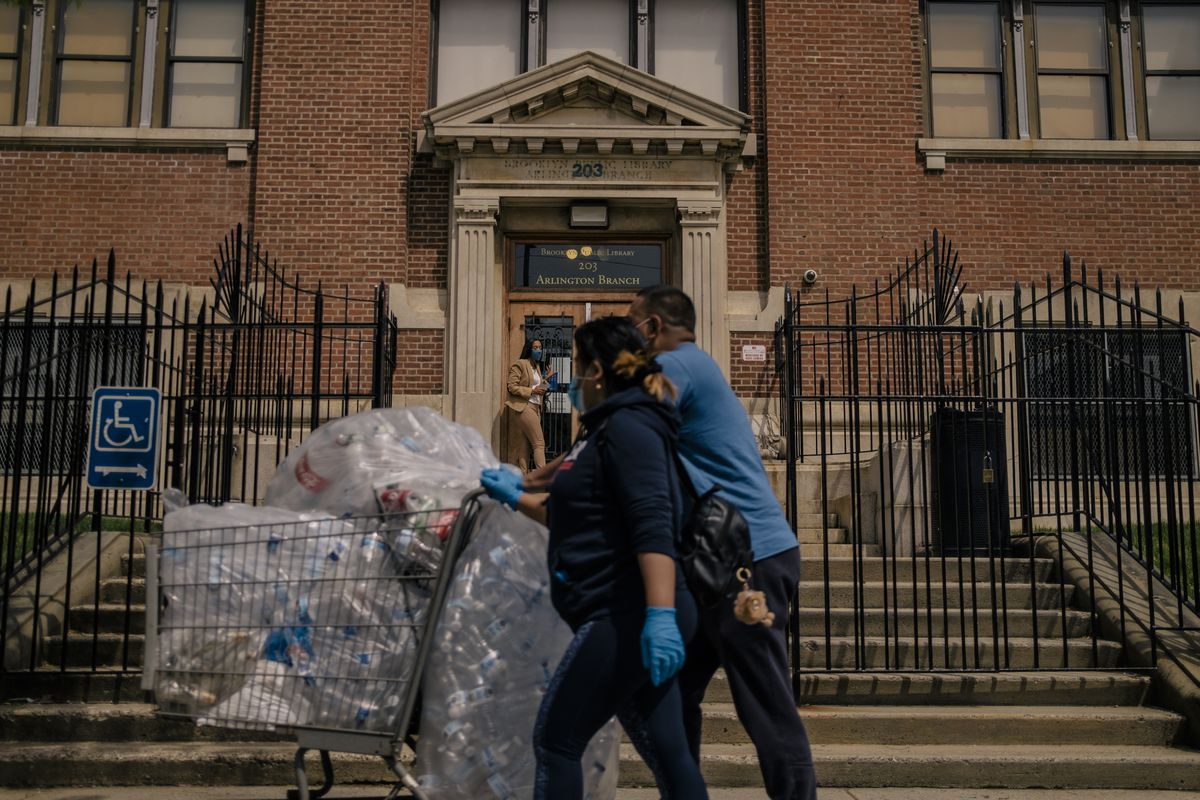 A couple push a cart filled with plastic bottles down the sidewalk, as a woman wearing a tan pantsuit walks out of a large brick building for the Brooklyn Public Library's Arlington branch.