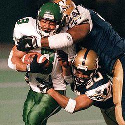 Saskatchewan Roughriders Darren Davis (8) is dragged down by Winnipeg Blue Bombers Harold Nash and Benny Goods (4) during first quarter CFL action in Winnipeg Friday, Sept. 29, 2000.