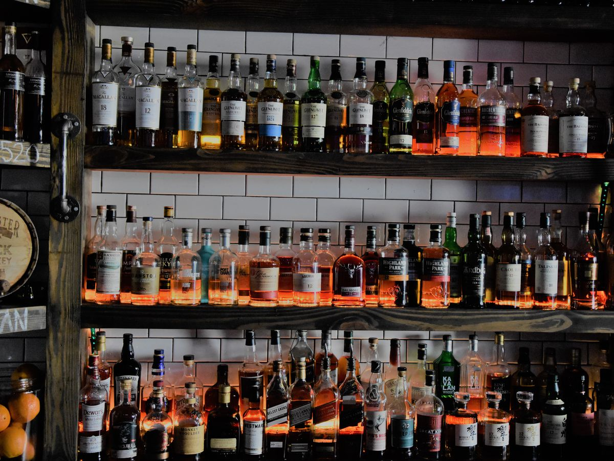 Three rows of wooden shelving, all containing bottles of whiskey