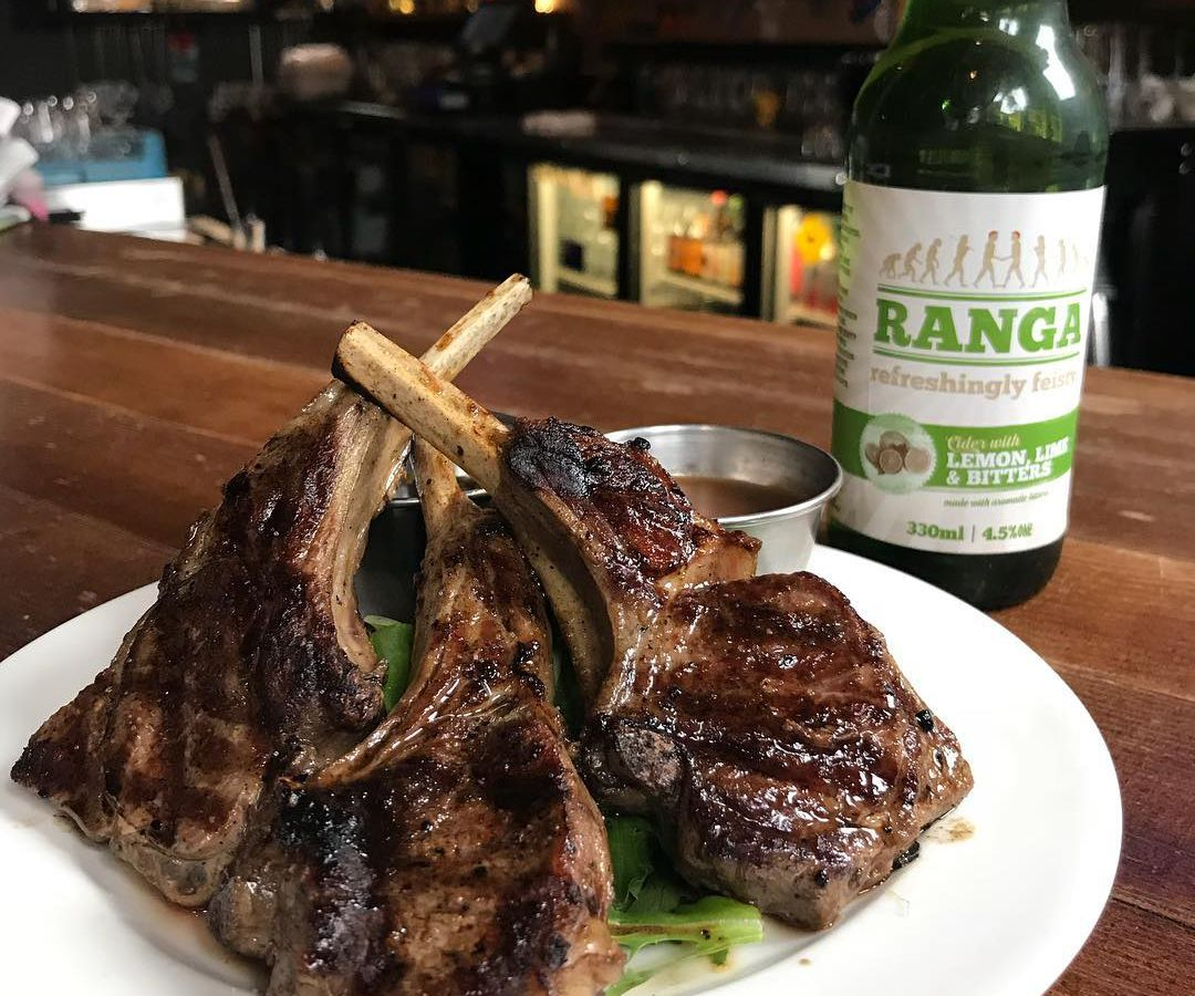 Lamb chops displayed on a white plate next to a bottle of beer.