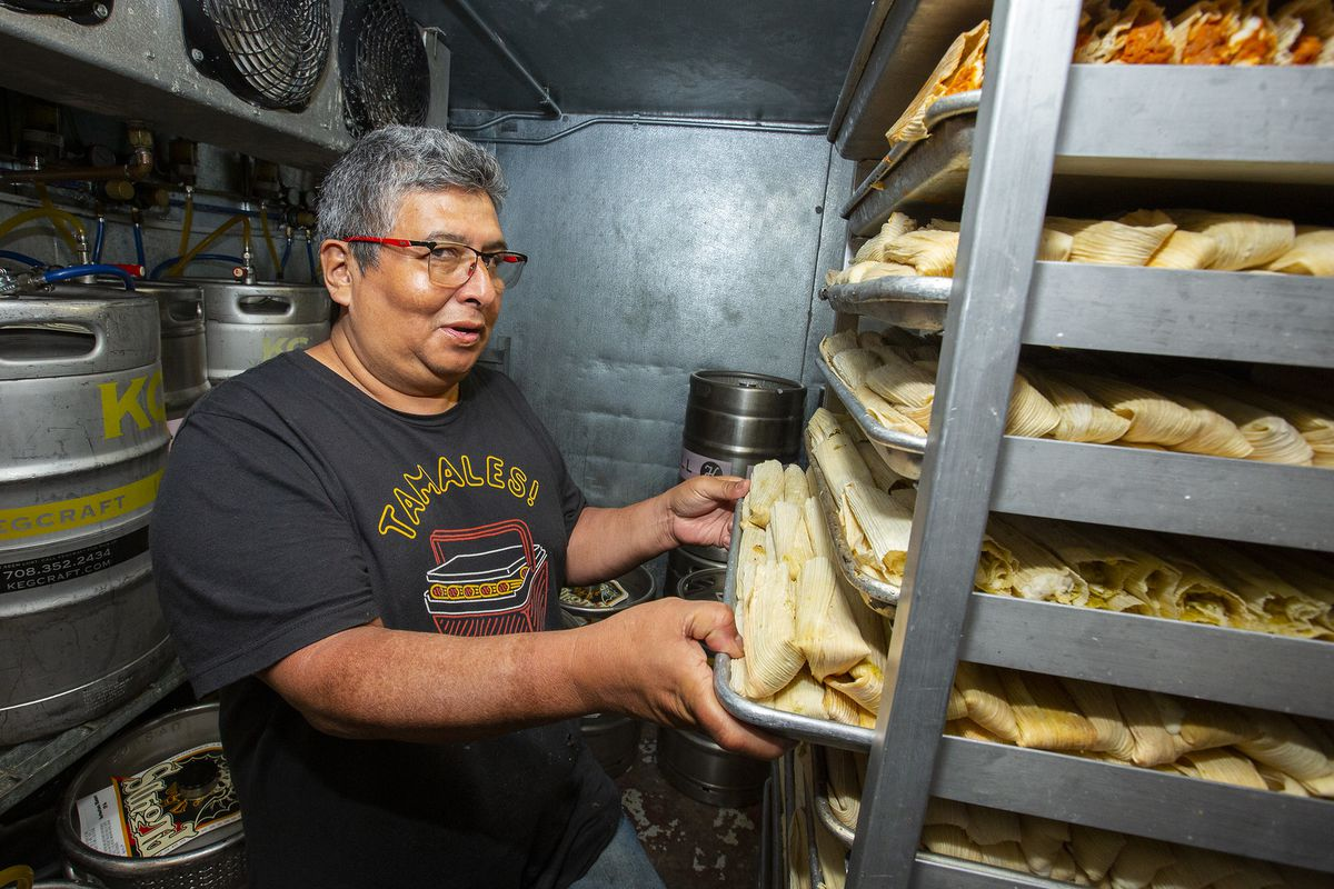 A smiling man with tamales.