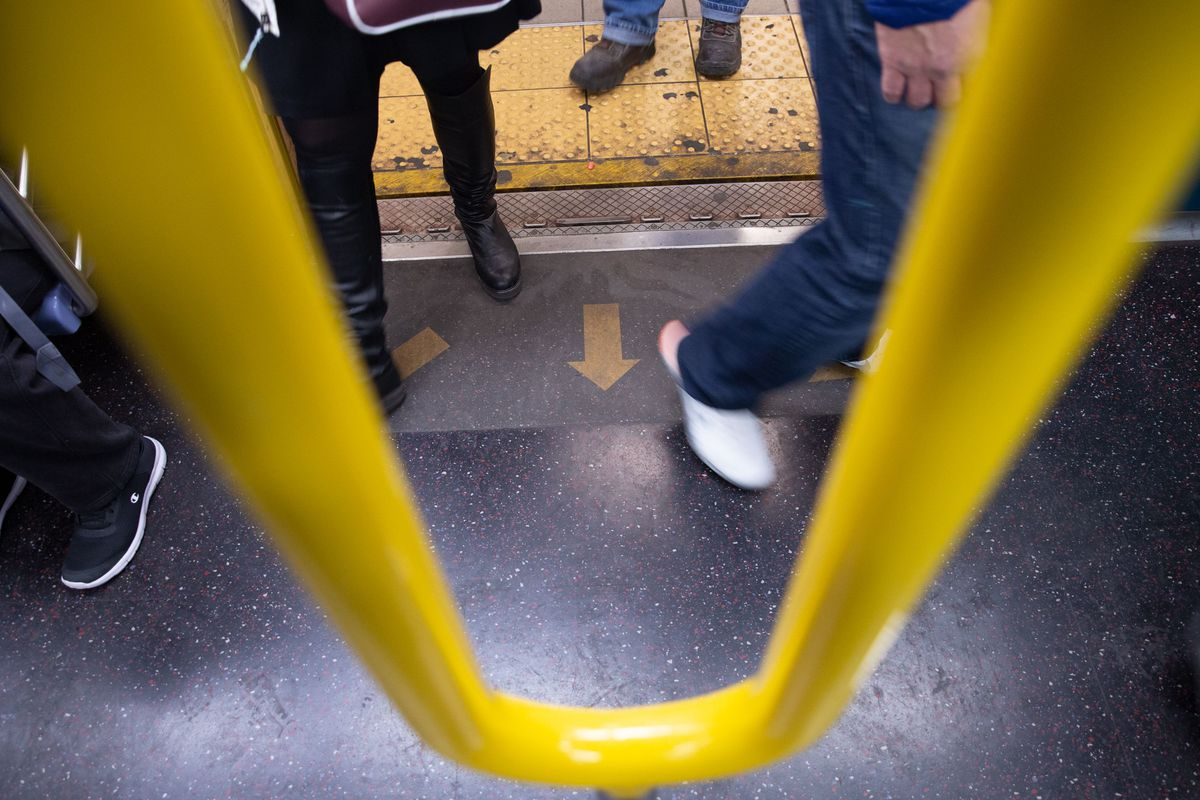 Passengers board an E train outfitted with directional stickers and a two-pronged pole, April 1, 2019.