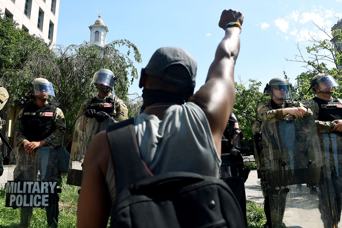 A person making the Black Power salute with fist raised faces a line of military police in riot gear.
