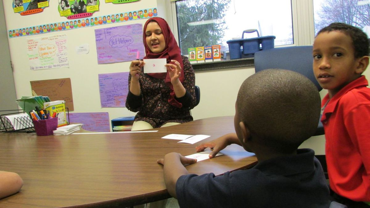 Immigrant students just arrived in the U.S. work on learning English words.