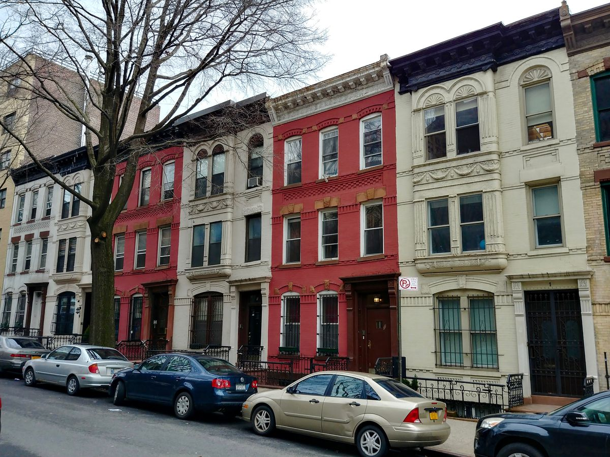 Hamilton Terrace in New York City. The street is lined with colorful row houses.