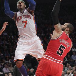 New York Knicks' Carmelo Anthony (7) goes to the basket past Chicago Bulls' Carlos Boozer during the first half of an NBA basketball game, Sunday, April 8, 2012, at Madison Square Garden in New York.