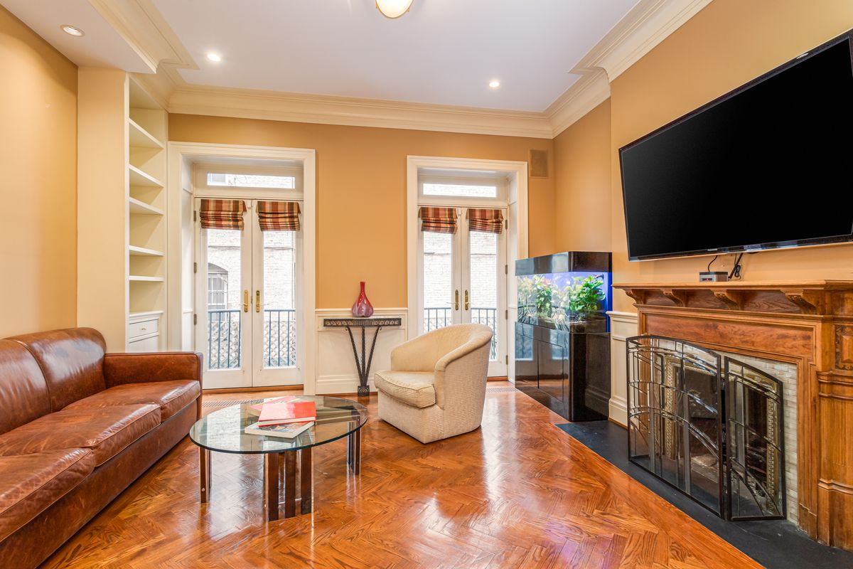 A living area with hardwood floors, a fireplace, a TV on the wall, a leather couch, and two doors that lead to a balcony.