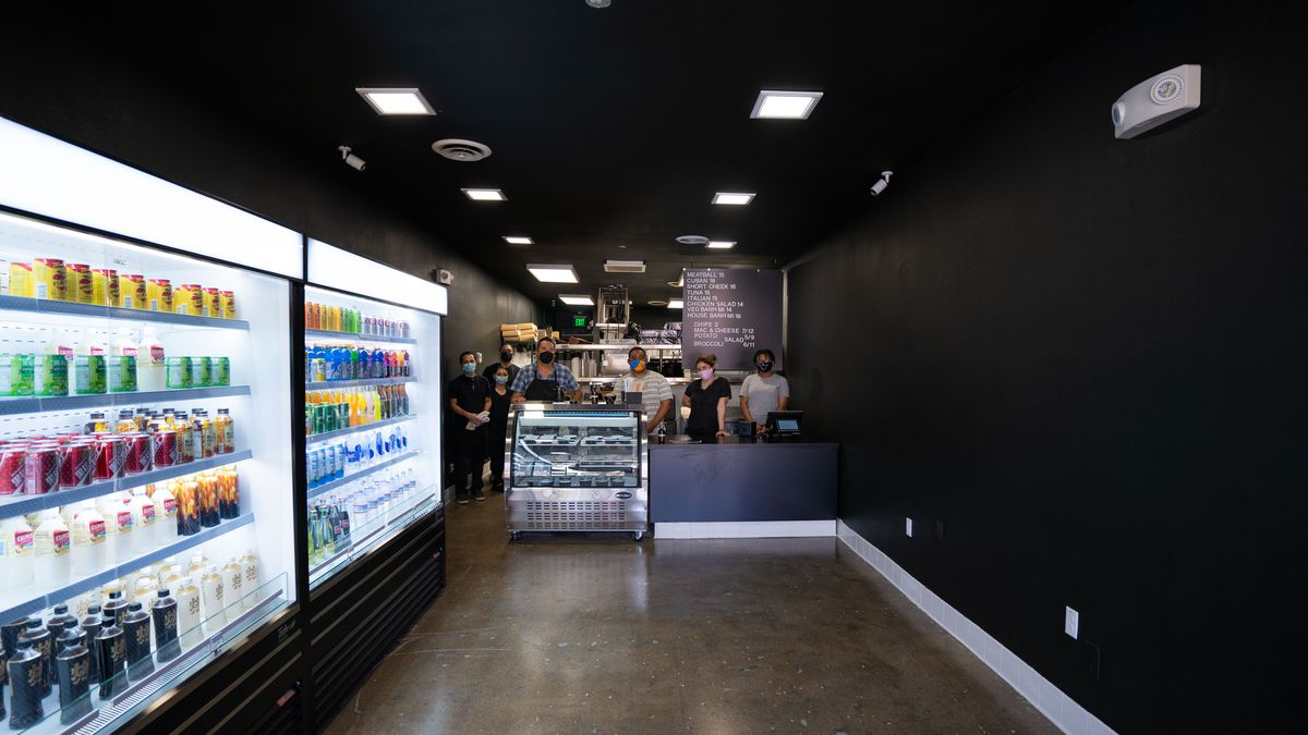 A black-painted new sandwich restaurant with no seating inside but a long wall of drinks.