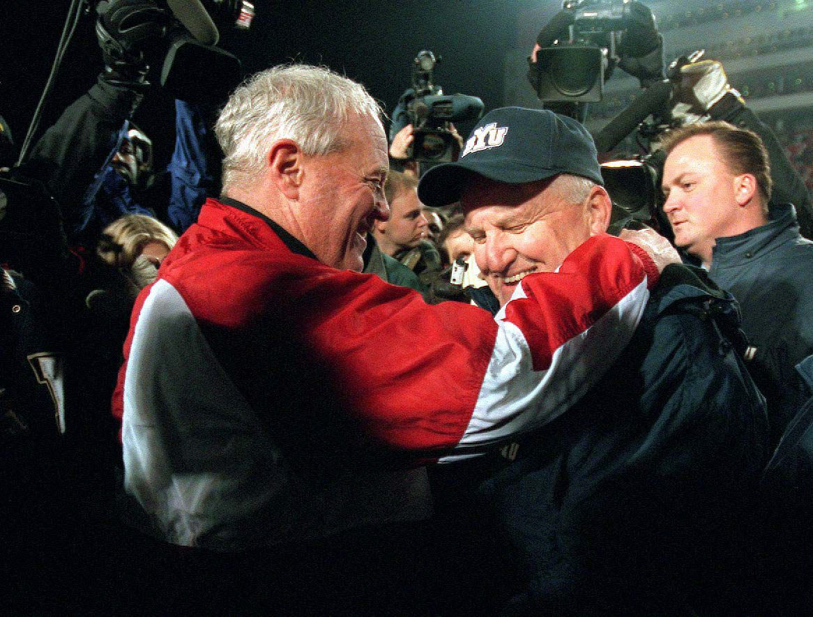 Ron McBride of the University of Utah congratulates LaVell Edwards of BYU after Edwards last game coaching football on Nov. 24, 2000.