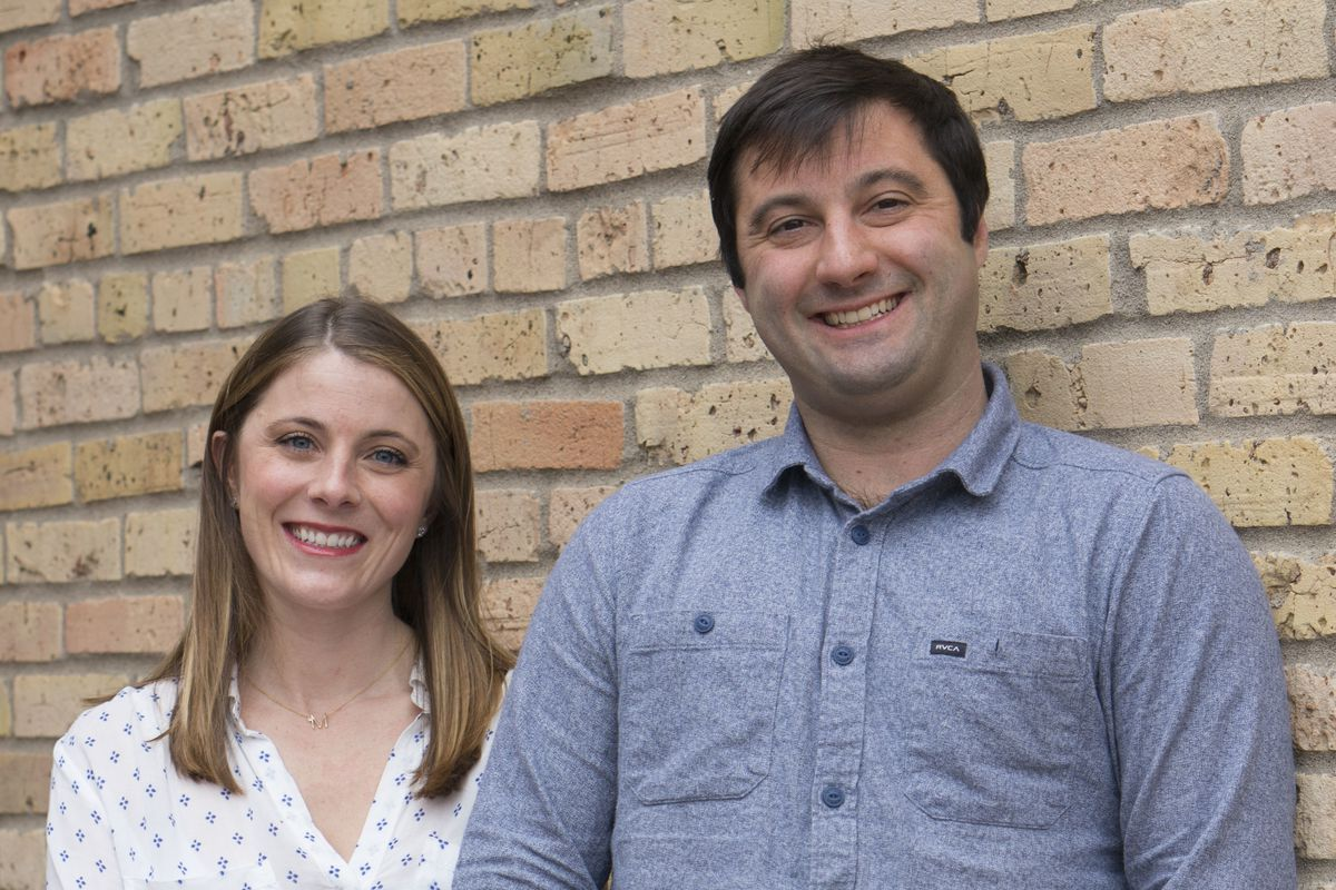 Two people standing against a brick wall, one with arms crossed and one with hands in pockets
