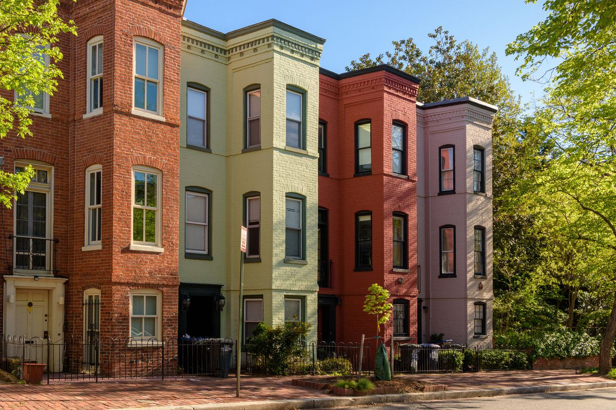 A row of colorful townhomes with large green trees surrounding them in a downtown district.