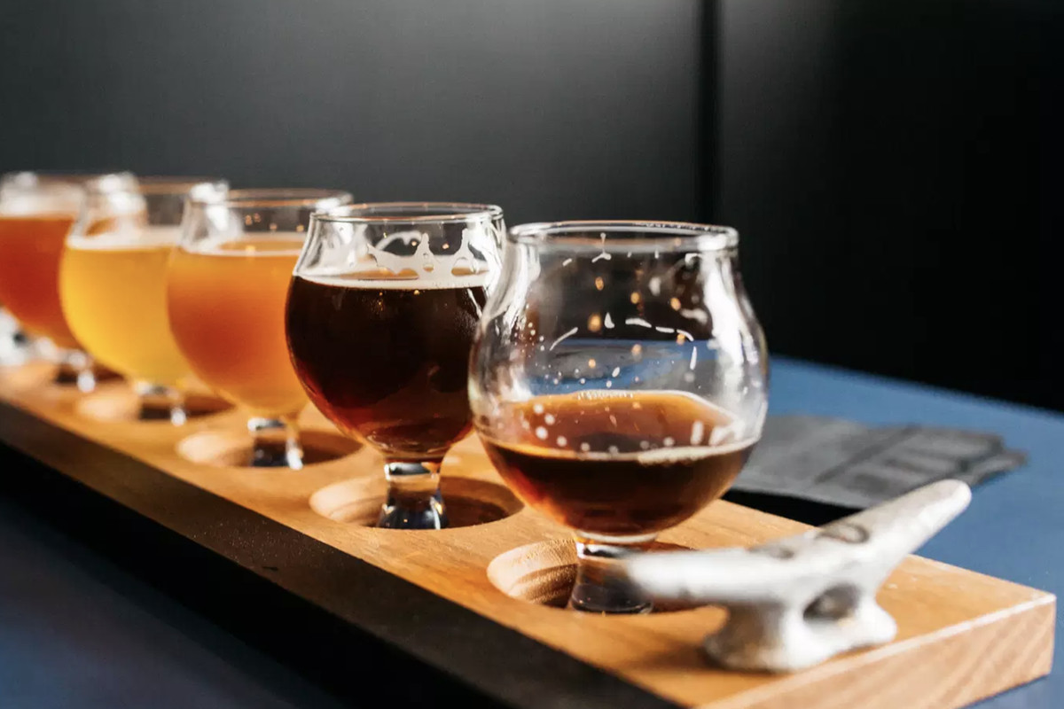 A flight of beers at Figurehead of varying color shades, with a mostly empty glass in the foreground