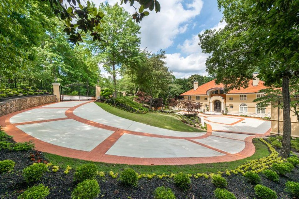 A winding driveway leads down to a Mediterranean-style mansion.