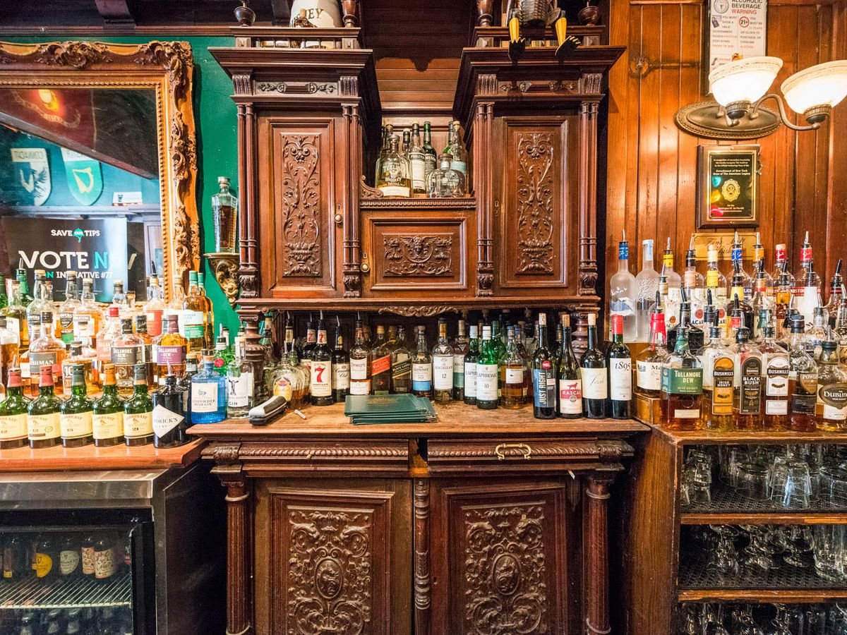 The wooden bar with dozens of bottles lined up in front of it at The Dubliner