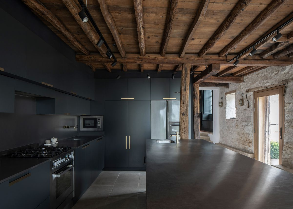 Kitchen featuring dark cabinets and timber beam ceiling.