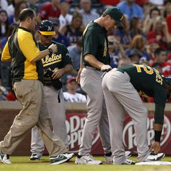 An Oakland Athletics staff member and manager Bob Melvin, center, check on Yoenis Cespedes (52) after Cespedes reached third on a run scoring triple off a pitch from Texas Rangers' Martin Perez in the first inning of a baseball game, Wednesday, Sept. 26, 2012, in Arlington, Texas. Cespedes remained in the game.