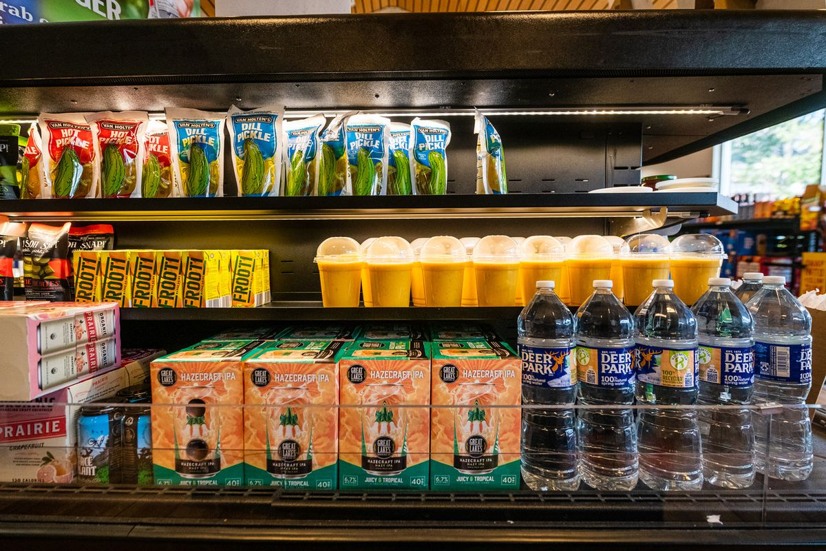 A refrigerated case contains plastic cups of mango lassi alongside boxes of beer and bottles of water.