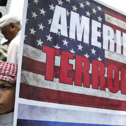 A Muslim youth pauses near a poster during a protest  against an anti-Islam film in Jakarta, Indonesia, Monday, Sept. 17, 2012. Indonesians enraged over an anti-Islam film hurled rocks and Molotov cocktails at the U.S. Embassy in Jakarta on Monday, marking the first violence in the world's most populous Muslim country since outrage exploded last week in the Middle East and beyond.