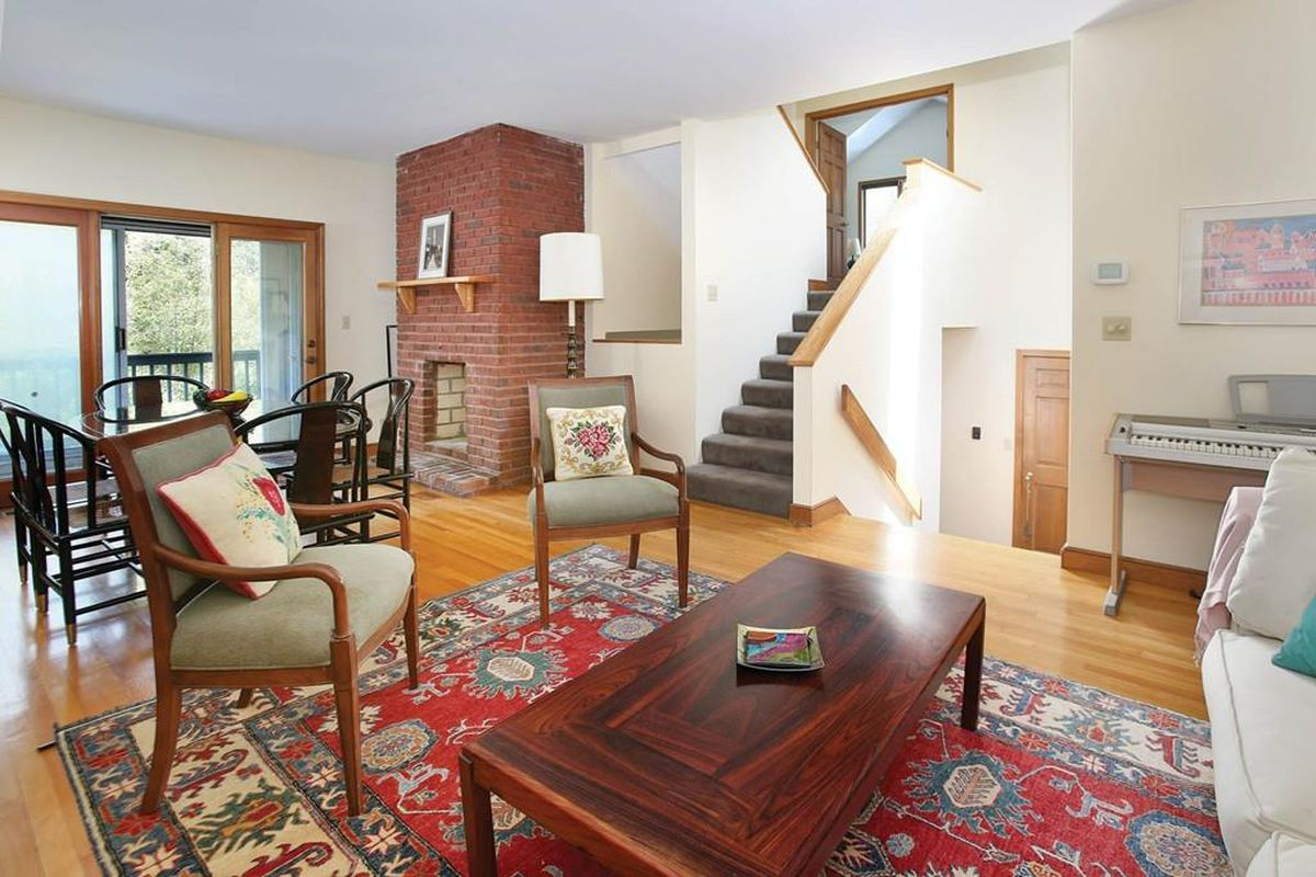 A spacious, airy living room with furniture and a brick column fireplace.