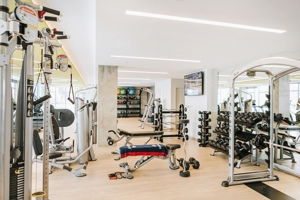 A modern gym with exercise machines and weights.