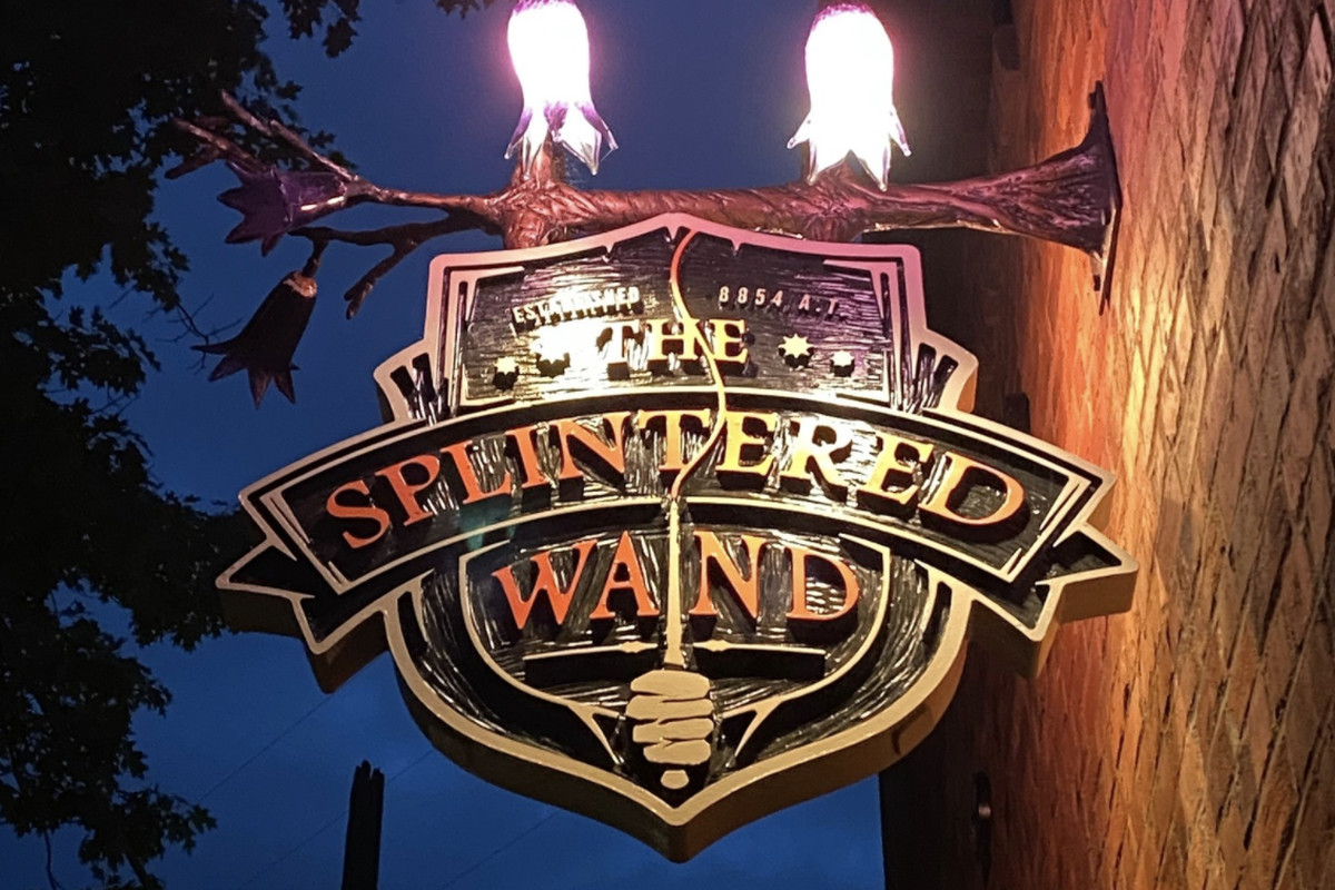 """A lighted sign in medieval style says """"The Splintered Wand"""""""