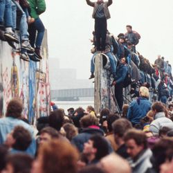 Berliners celebrate on top of the wall as East Germans, backs to camera, flood through the dismantled Berlin Wall at Potsdamer Platz on Nov. 12, 1989.