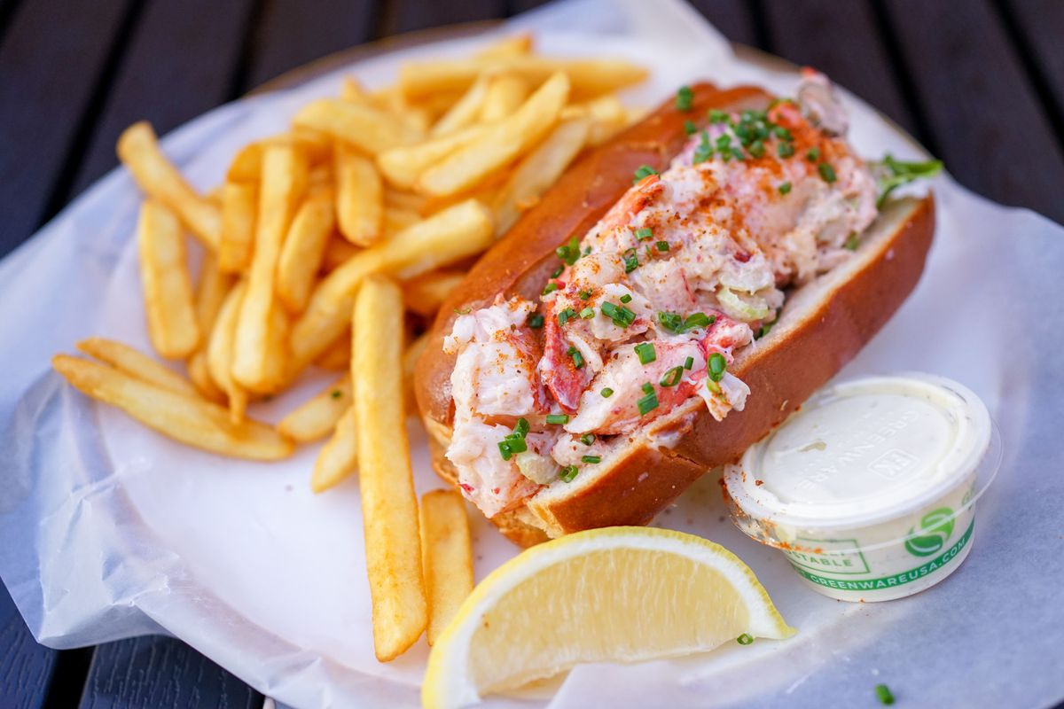 A close-up of a lobster roll with a side of fries, alongside a wedge of lemon and tartar sauce